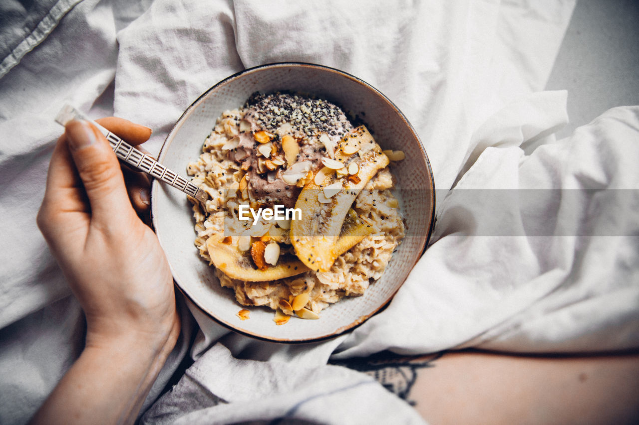 Close-Up Of Hand Eating Granola In Bowl On Bed