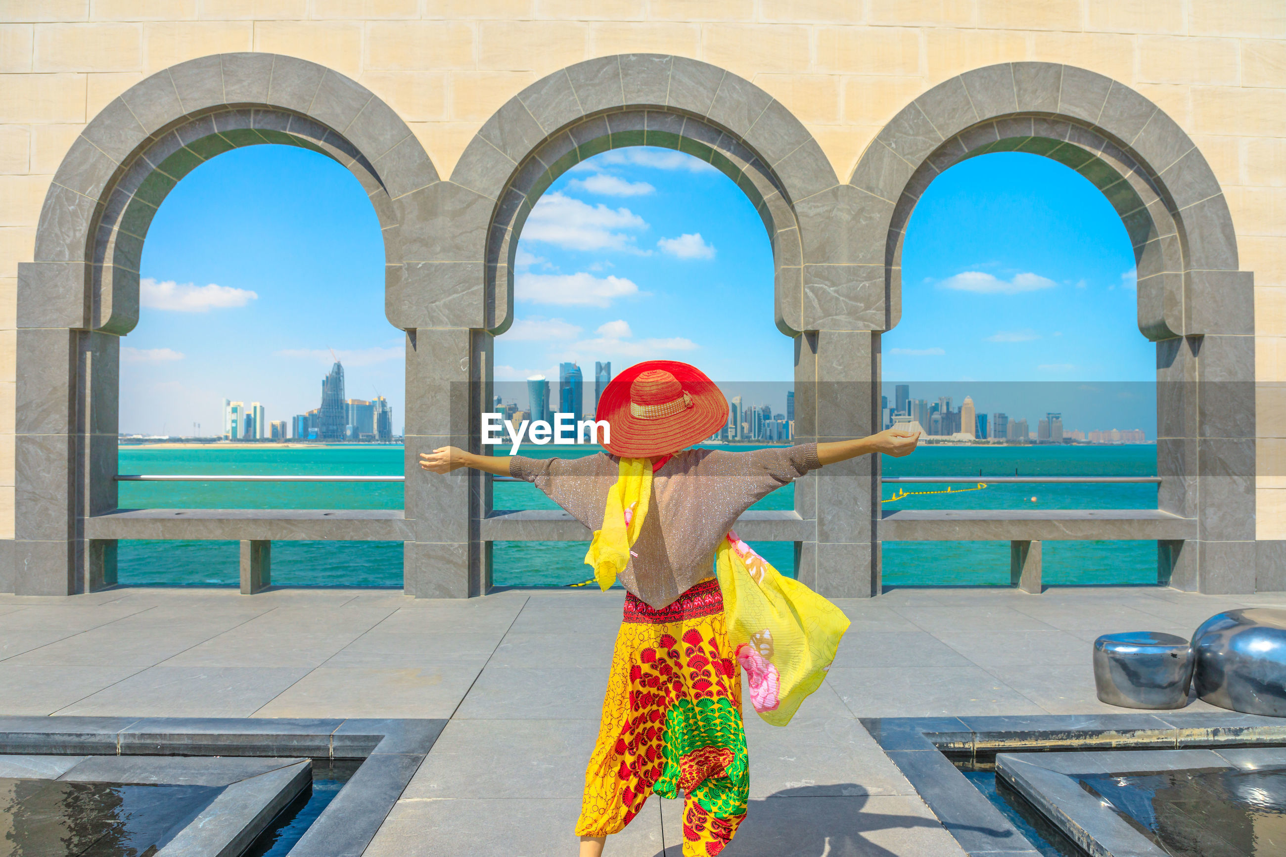 Woman with arms outstretched standing against arch in city
