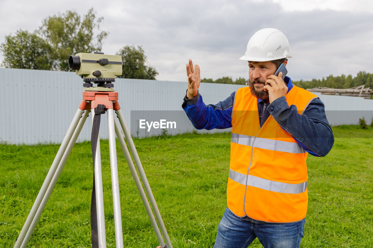 A disgruntled civil engineer with an optical level gauge speaks on a cell phone and swears.