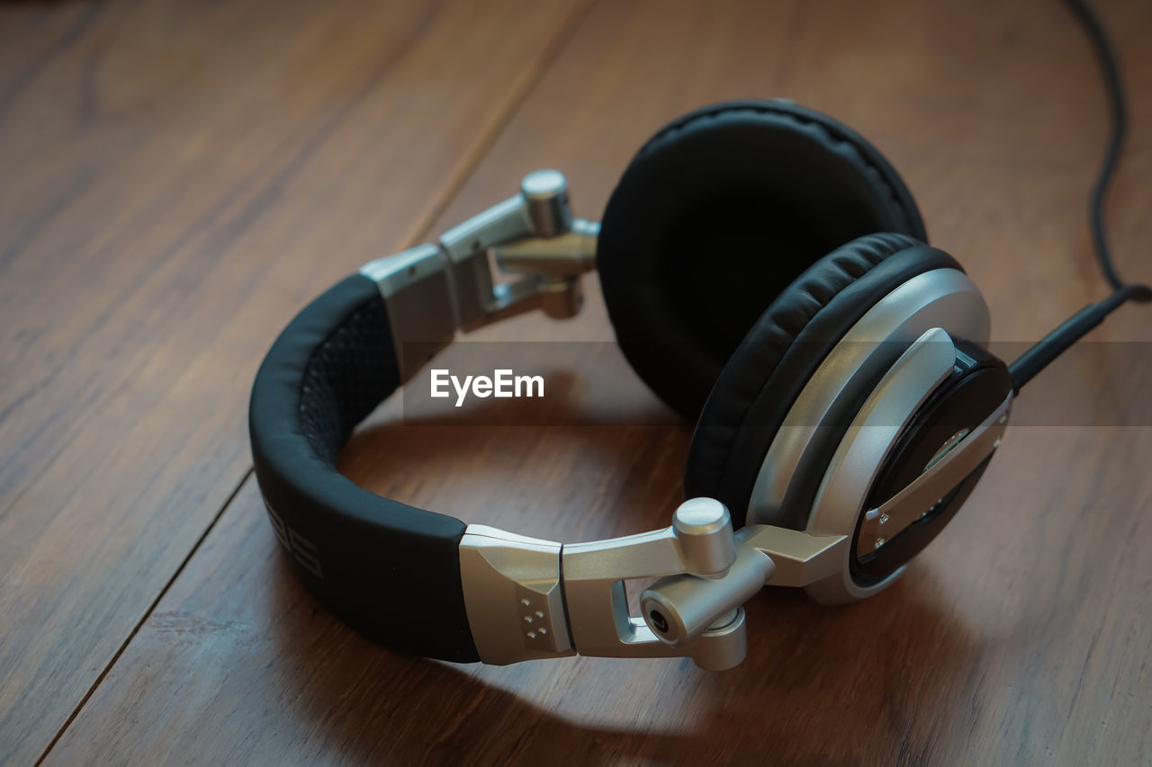 High angle view of headphones on wooden table