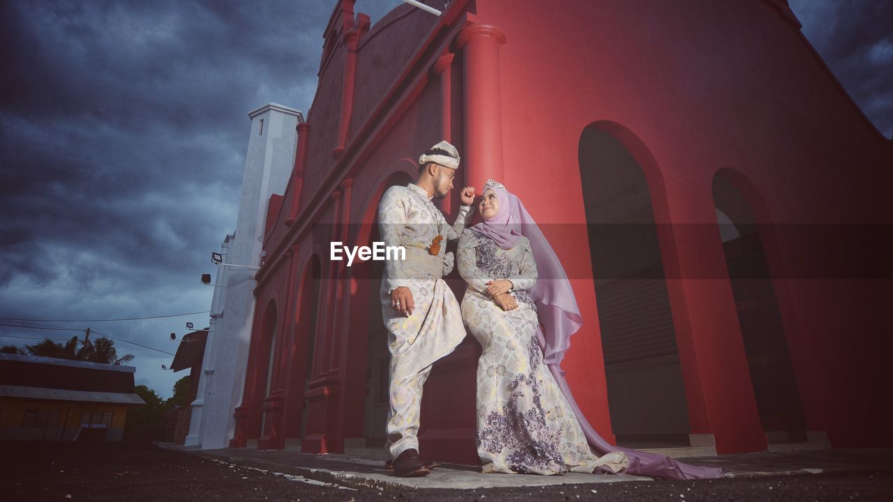 human representation, built structure, architecture, statue, building exterior, sculpture, full length, religion, outdoors, sky, real people, standing, two people, low angle view, togetherness, women, day, bride, wedding dress, groom, people