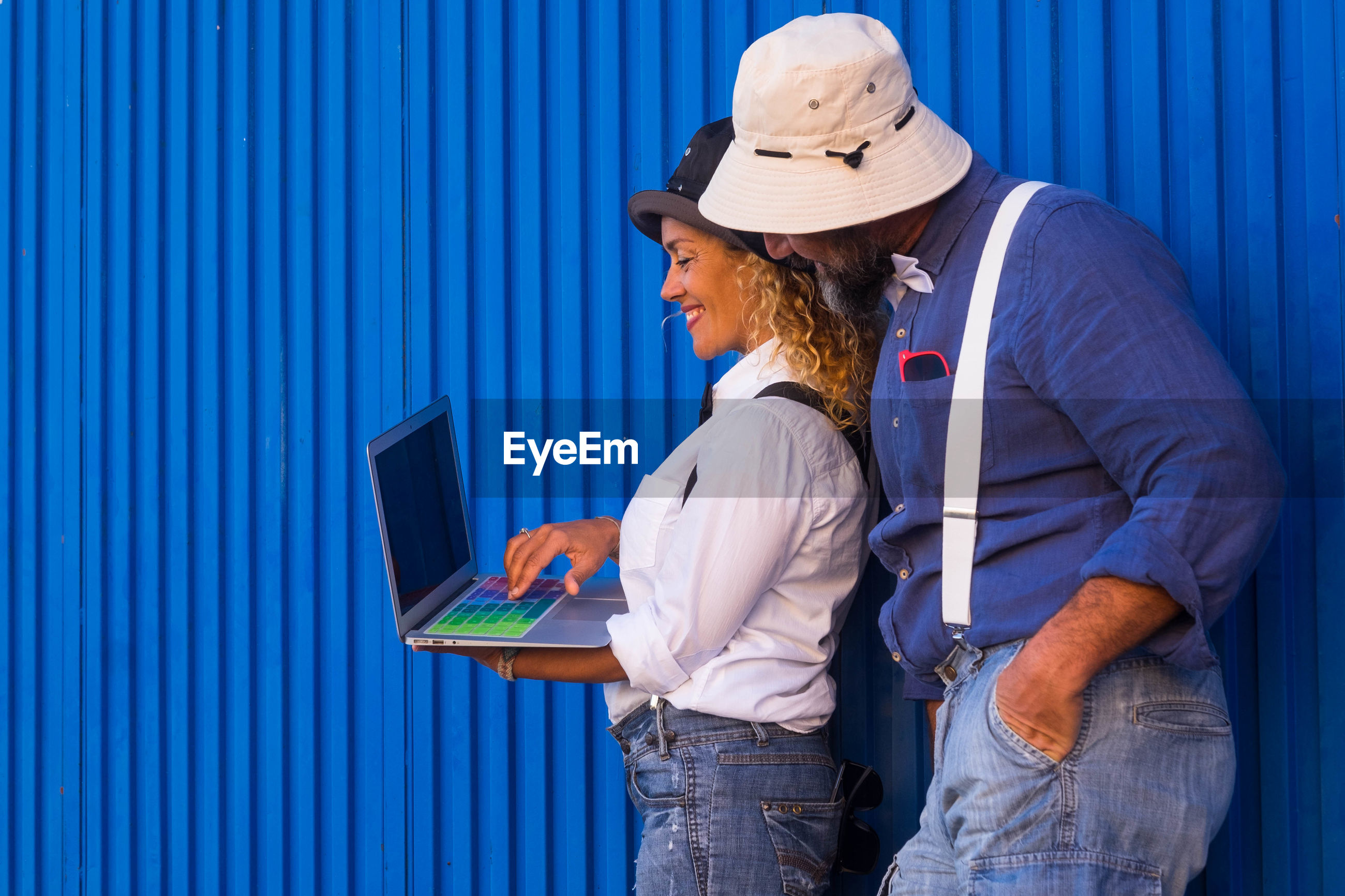 Couple using laptop while standing against corrugated iron
