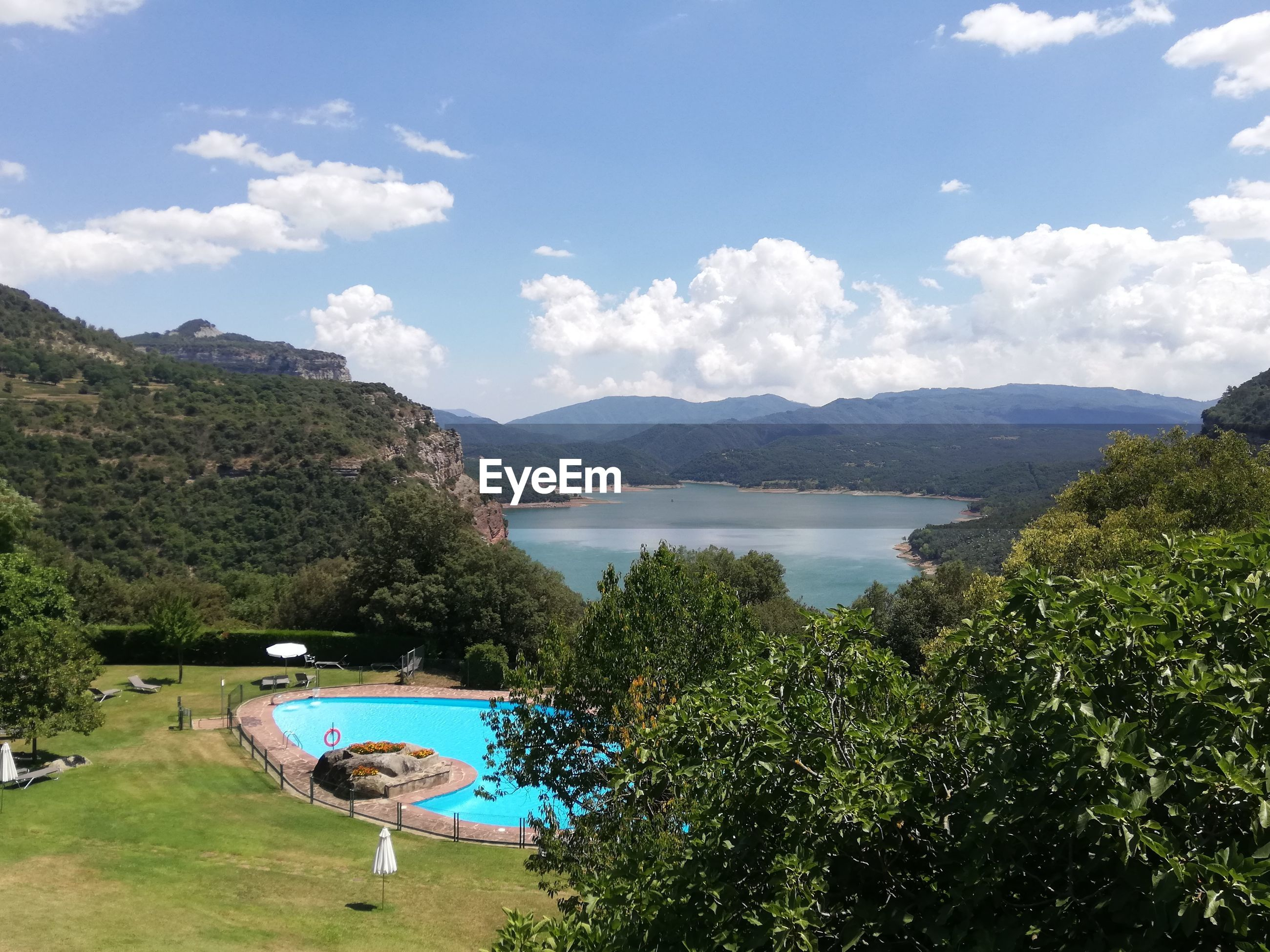 HIGH ANGLE VIEW OF SWIMMING POOL BY TREE MOUNTAINS AGAINST SKY