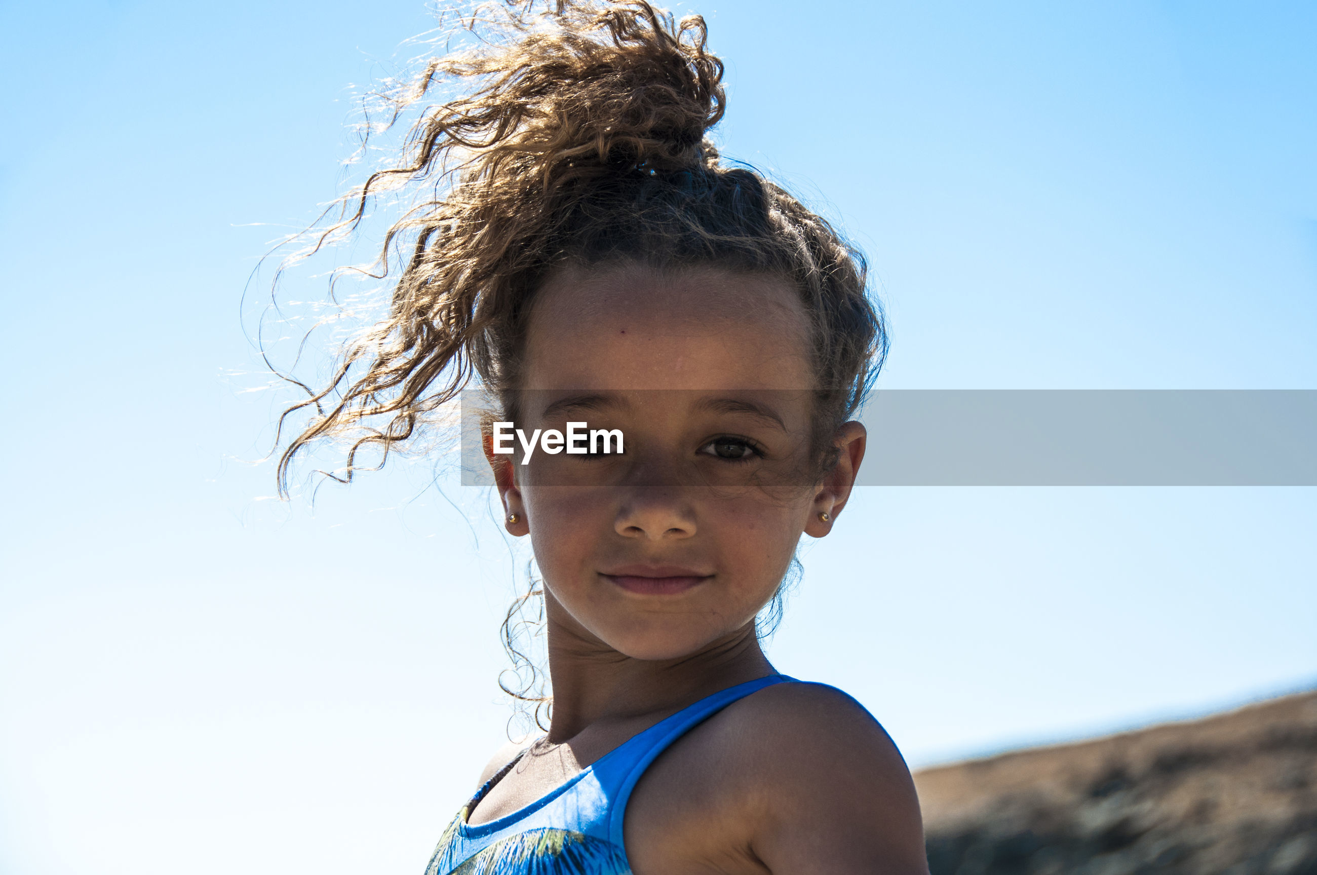 Portrait of confident girl with curly hair standing against clear sky