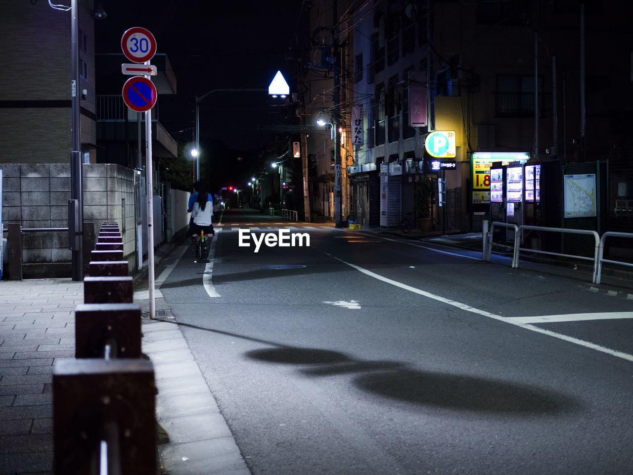 VEHICLES ON ROAD AT ILLUMINATED CITY STREET