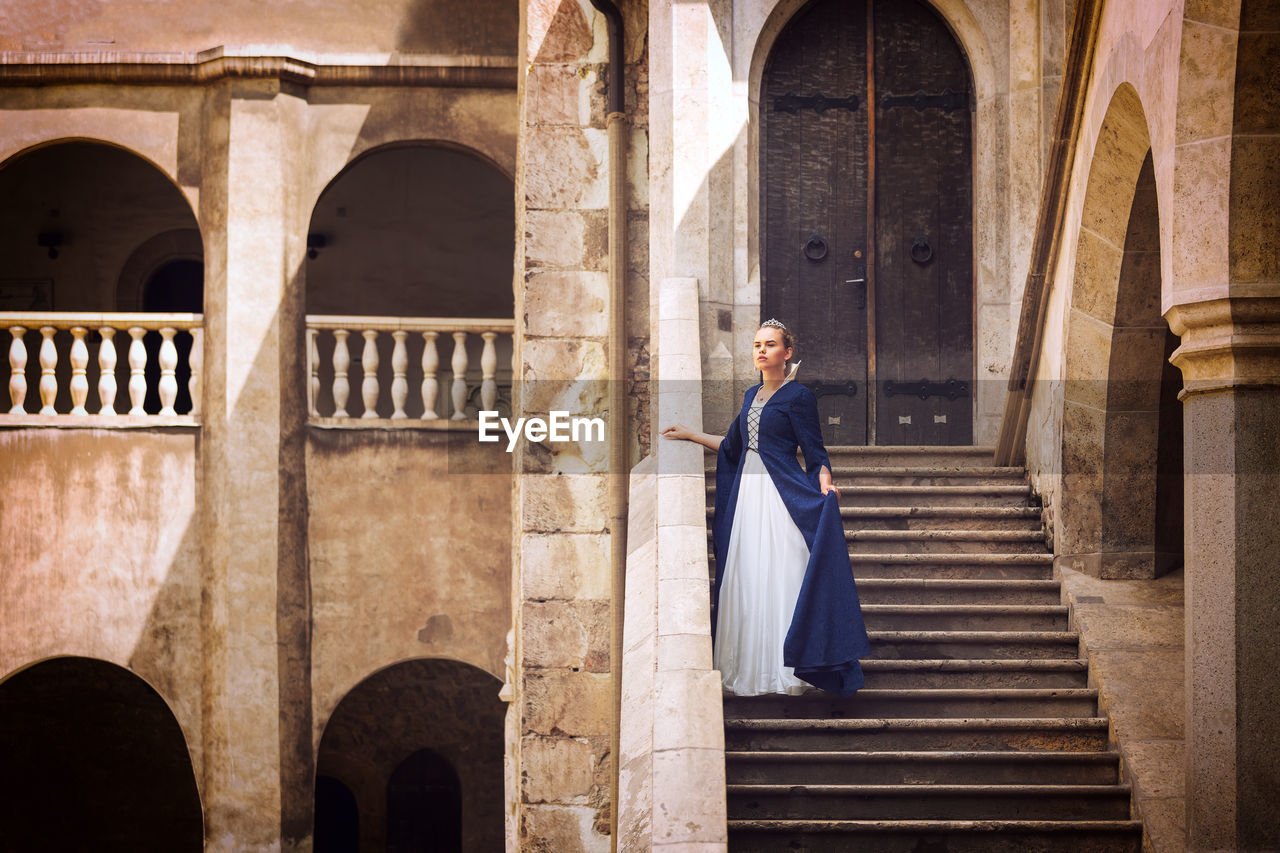 Young beautiful princess or queen standing on steps of medieval castle
