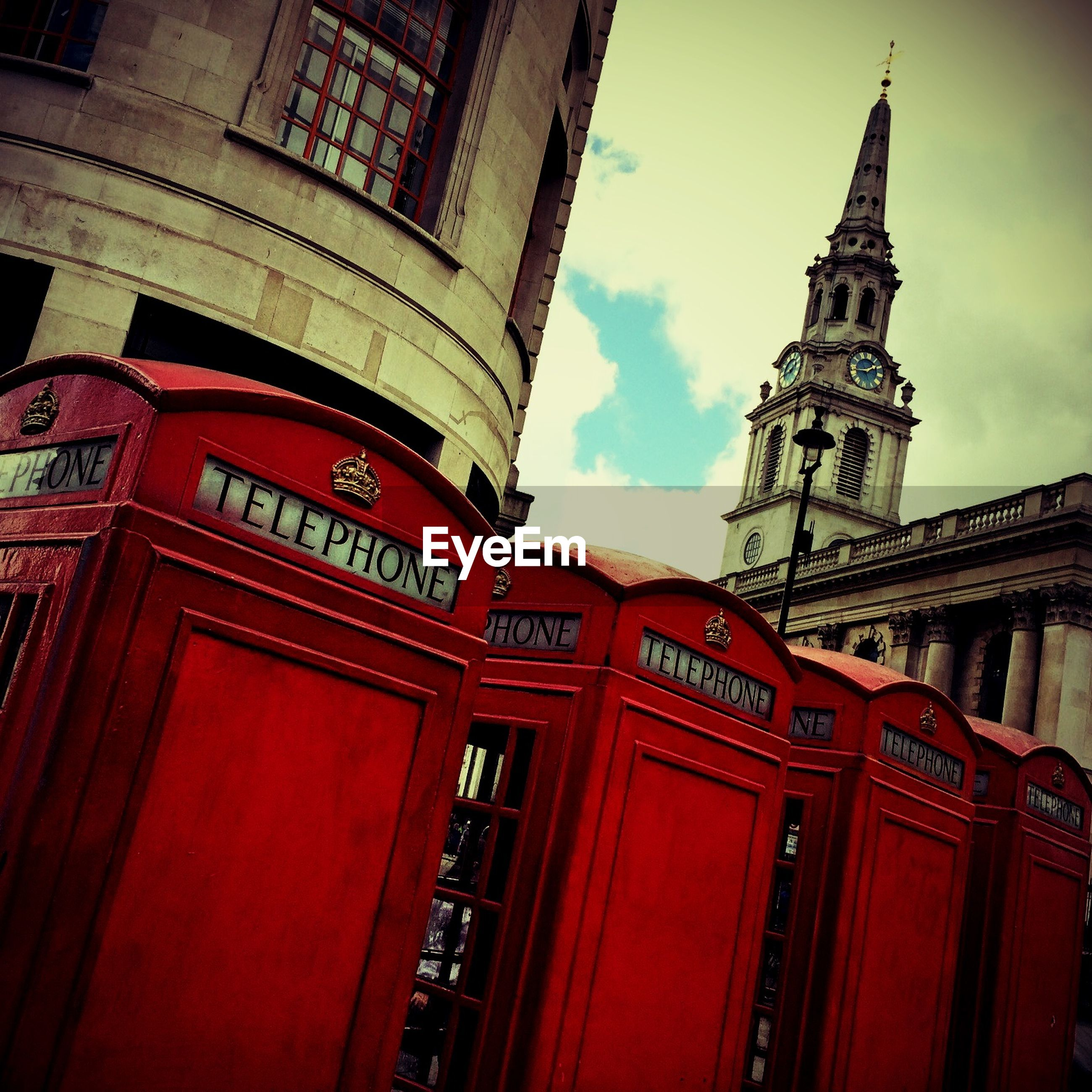 Low angle view of telephone booths against clock tower and buildings