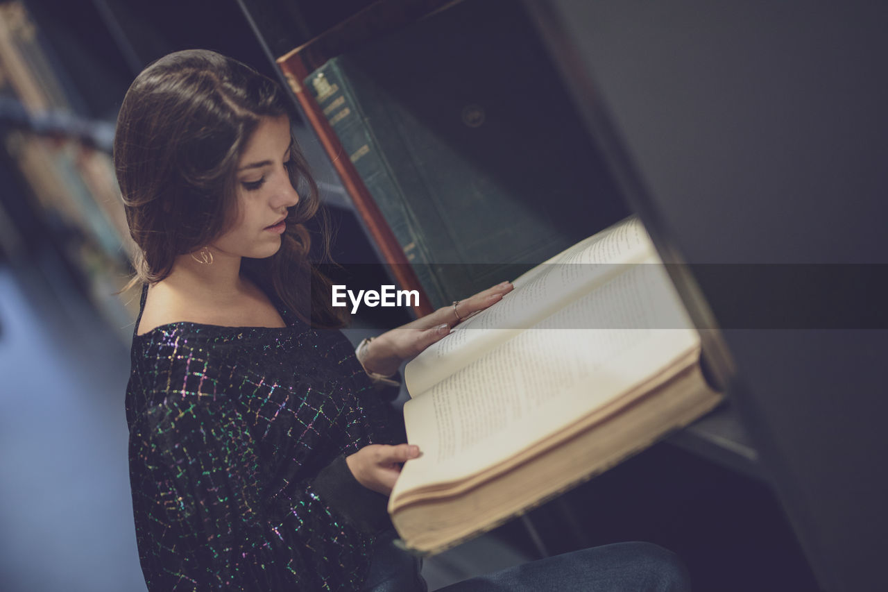 High angle view of young woman reading book at library