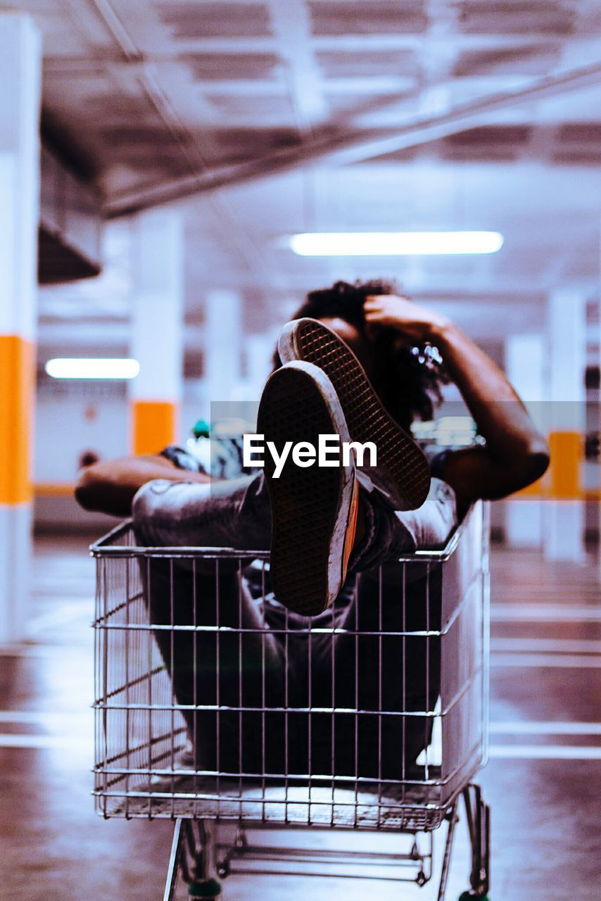 Man Sitting In Shopping Cart