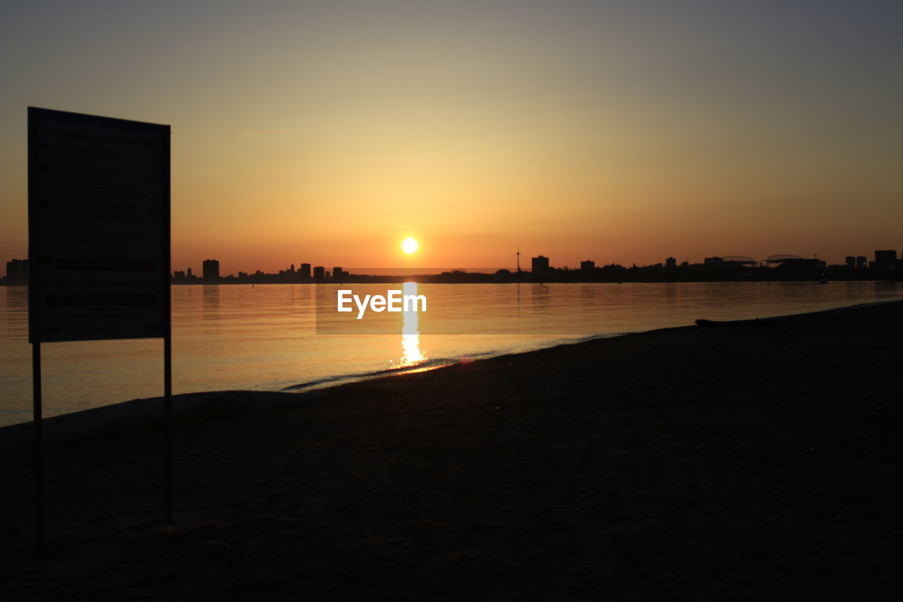 sunset, sky, water, silhouette, orange color, sun, scenics - nature, beauty in nature, tranquility, architecture, tranquil scene, nature, built structure, sea, building exterior, no people, beach, sunlight, copy space, outdoors
