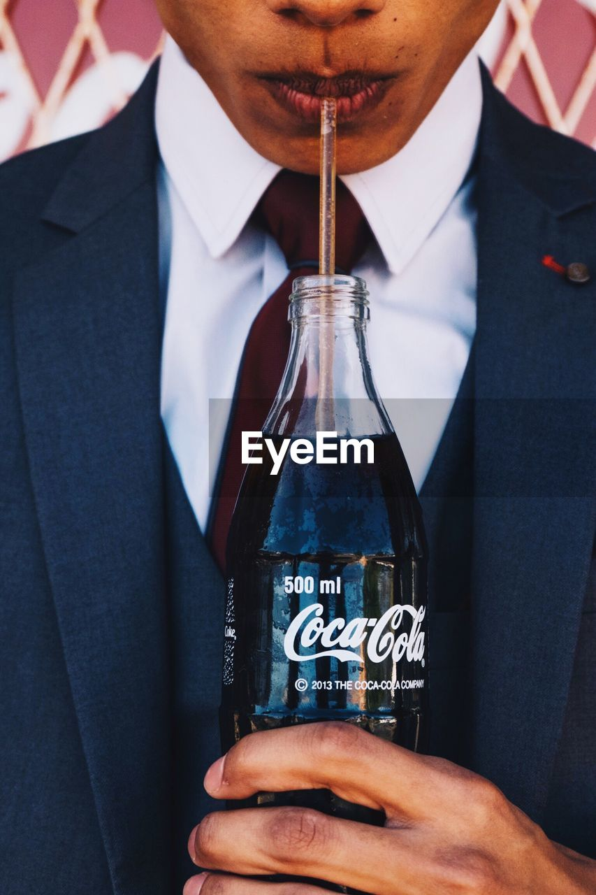 businessman, midsection, real people, text, one person, men, well-dressed, necktie, suit, business, indoors, close-up, lifestyles, drink, one man only, groom, day, human hand, people