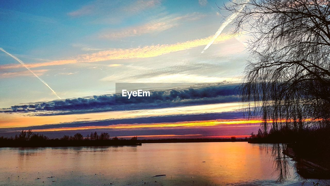 sunset, sky, reflection, scenics, beauty in nature, nature, water, cloud - sky, tranquil scene, no people, tranquility, vapor trail, outdoors, tree, lake, day