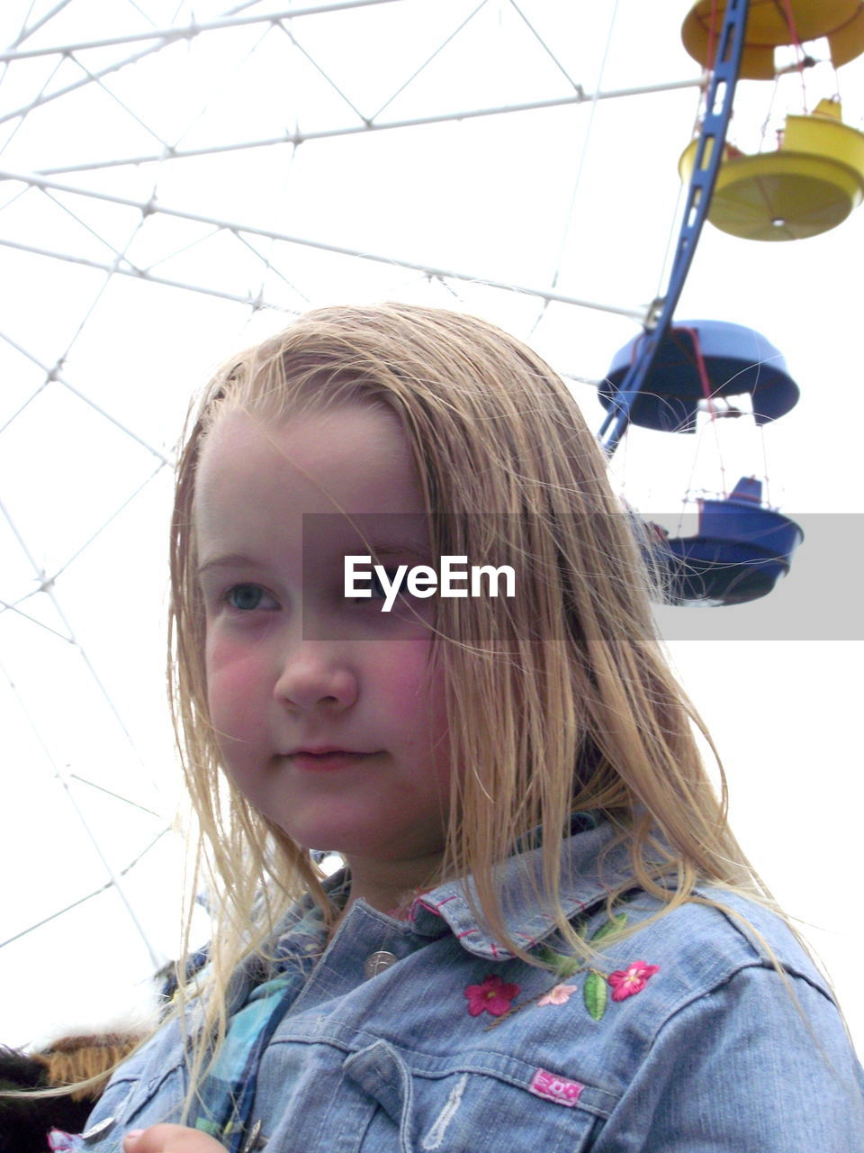 Close-up of girl looking away while standing against ferris wheel