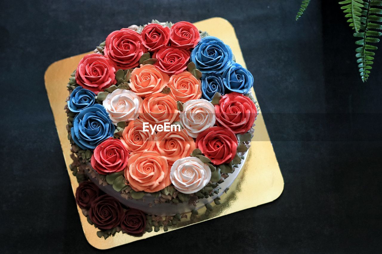 HIGH ANGLE VIEW OF MULTI COLORED ROSE ON TABLE