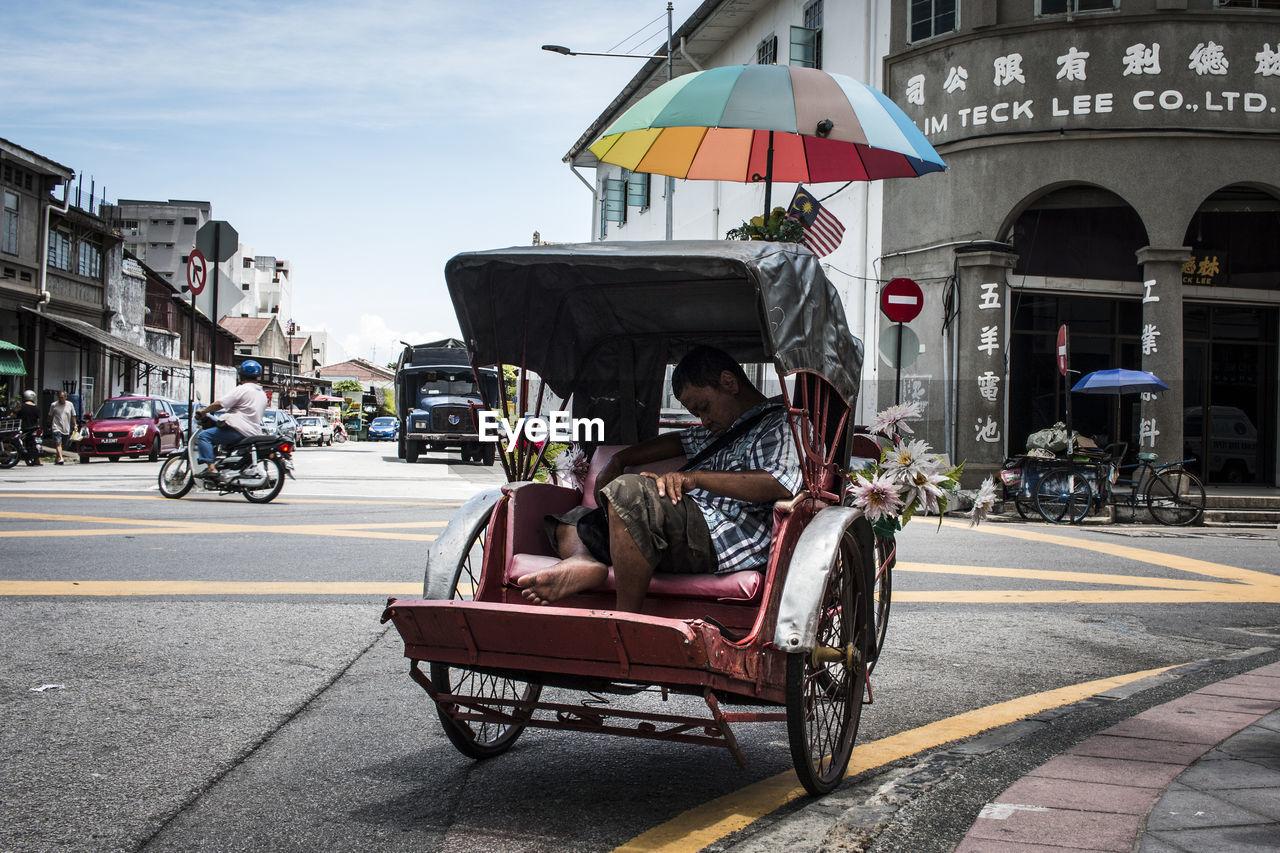 PEOPLE SITTING ON ROAD