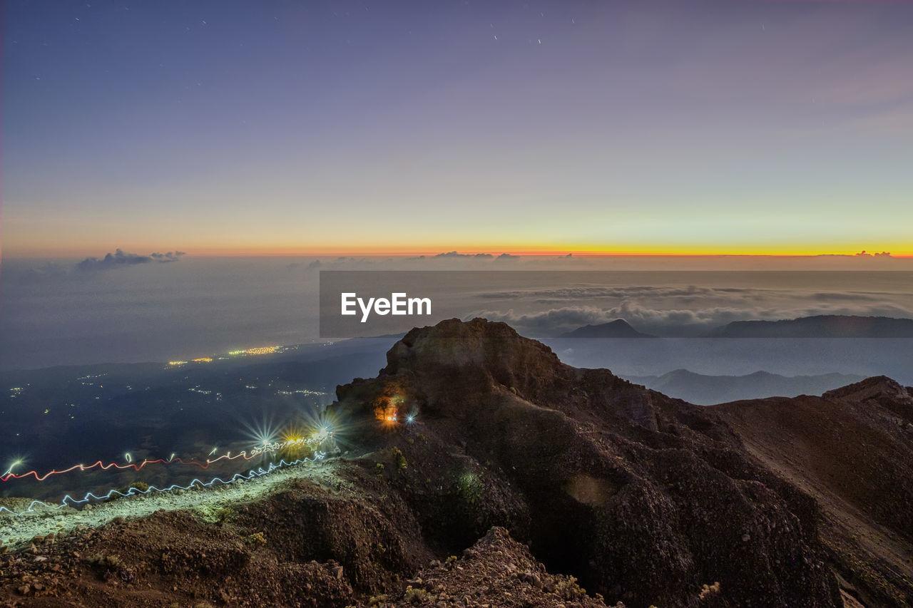 Light trails on summit mount rinjani against majestic sky