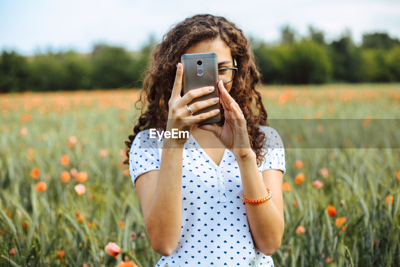 Midsection of woman photographing with smart phone in field