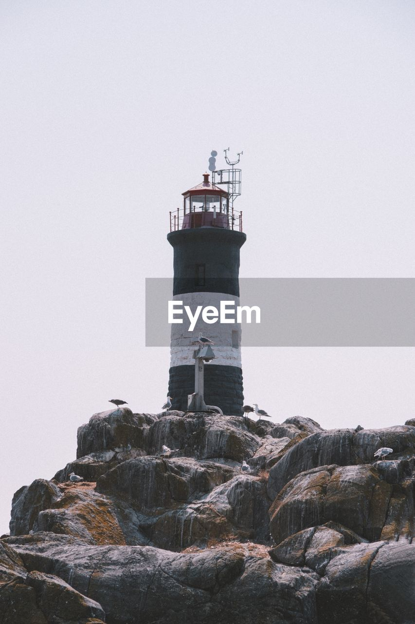 lighthouse, tower, architecture, building exterior, guidance, direction, built structure, protection, security, rock, sky, building, nature, safety, copy space, rock - object, no people, clear sky, solid, outdoors