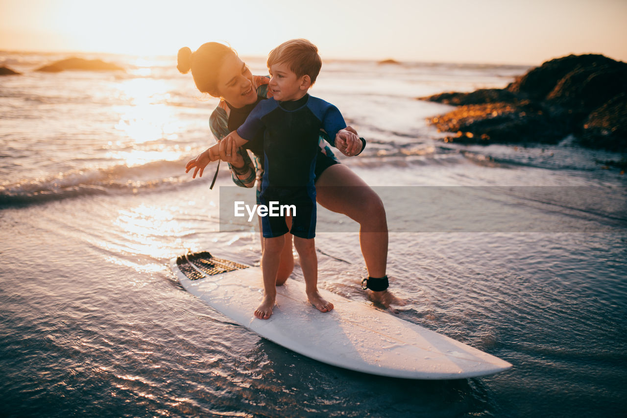 water, sea, men, childhood, child, males, boys, leisure activity, two people, real people, full length, togetherness, sky, lifestyles, land, family, beach, nature, horizon over water, son, positive emotion, outdoors