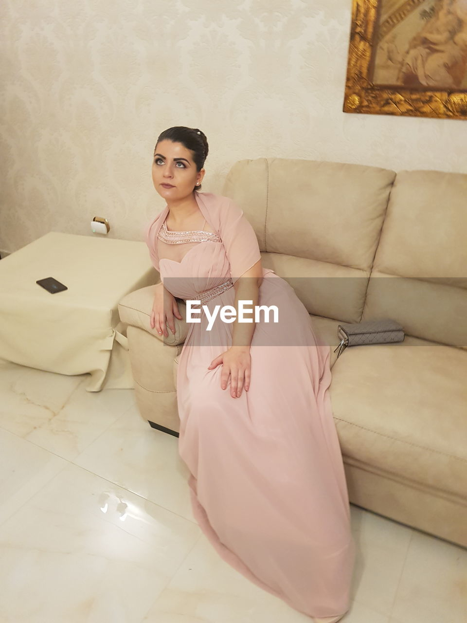 furniture, indoors, sofa, sitting, one person, domestic room, full length, lifestyles, home interior, looking at camera, women, young women, real people, young adult, leisure activity, front view, beautiful woman, relaxation, beauty, flooring