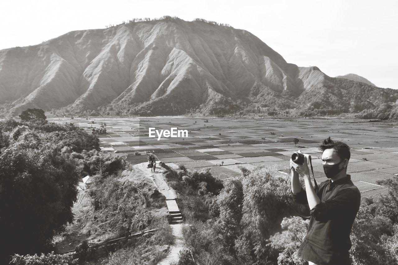 Man wearing flu mask photographing against mountain range