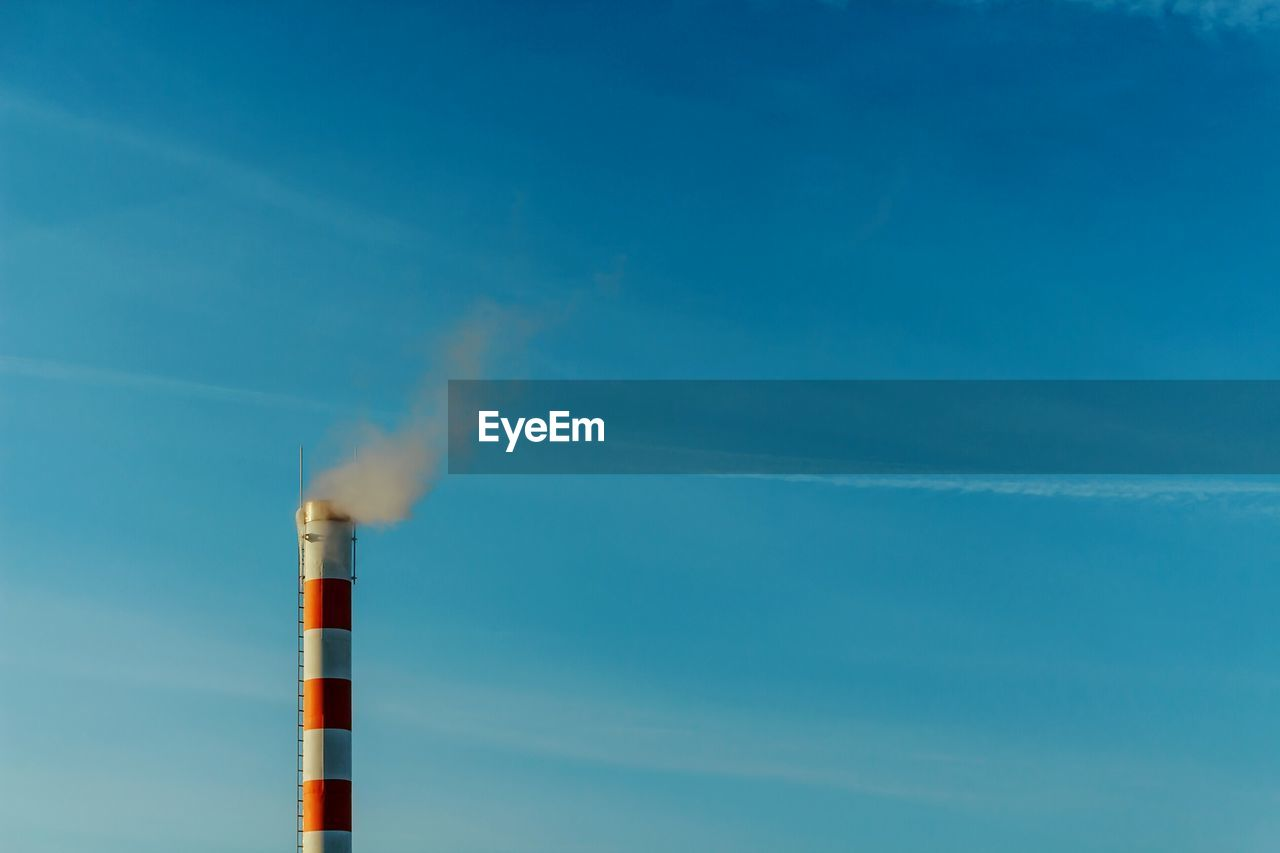 smoke - physical structure, factory, smoke stack, sky, pollution, industry, environmental issues, air pollution, building exterior, environment, blue, cloud - sky, day, vapor trail, nature, emitting, outdoors, no people, motion, built structure, fumes, poisonous