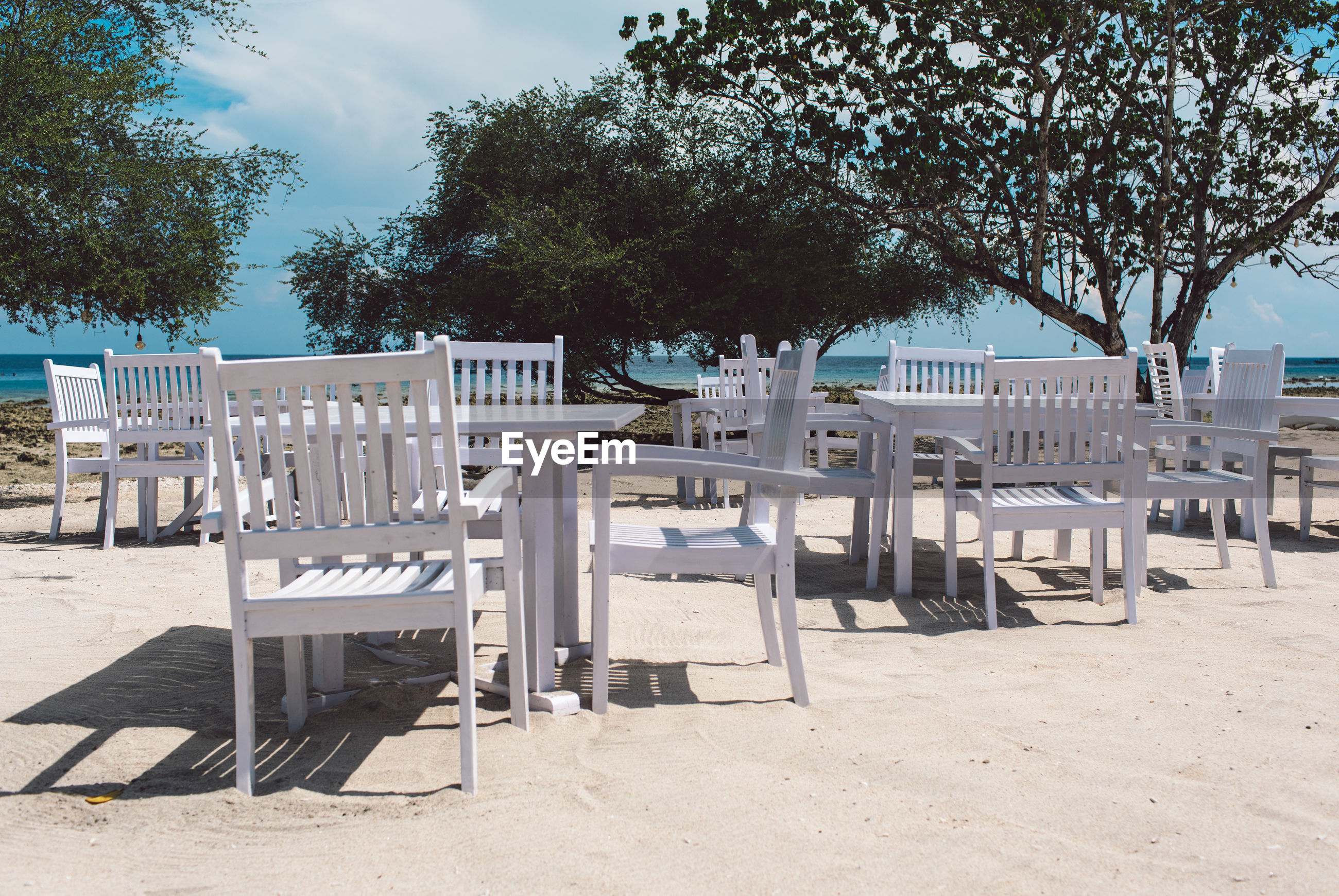 EMPTY CHAIRS AND TABLES ON BEACH