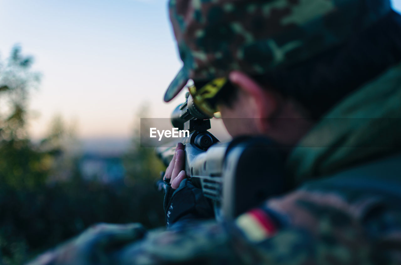 Close-Up Of Army Soldier Aiming With Sniper During Sunset