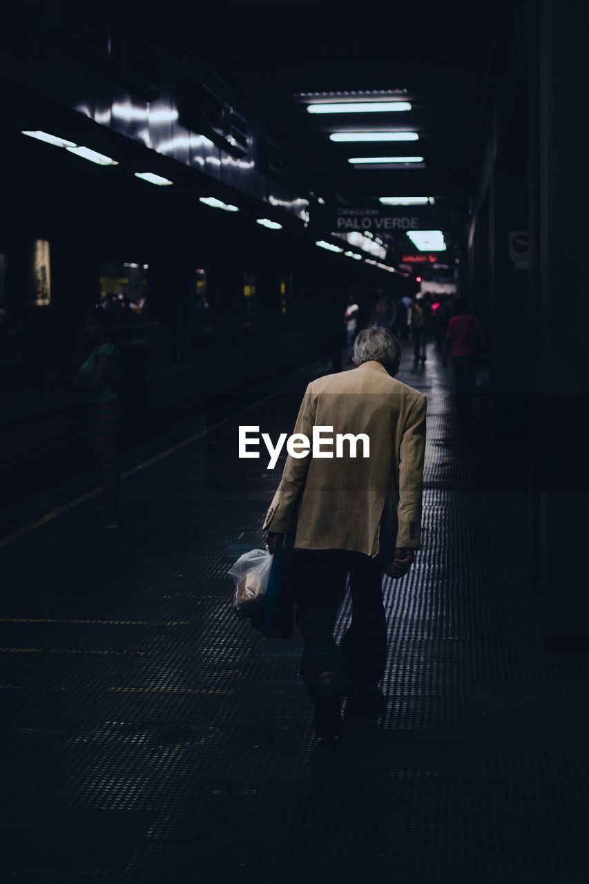 Rear view of man walking on at subway station
