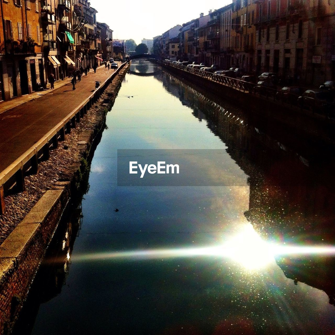 Reflection of sun in canal amidst buildings in city