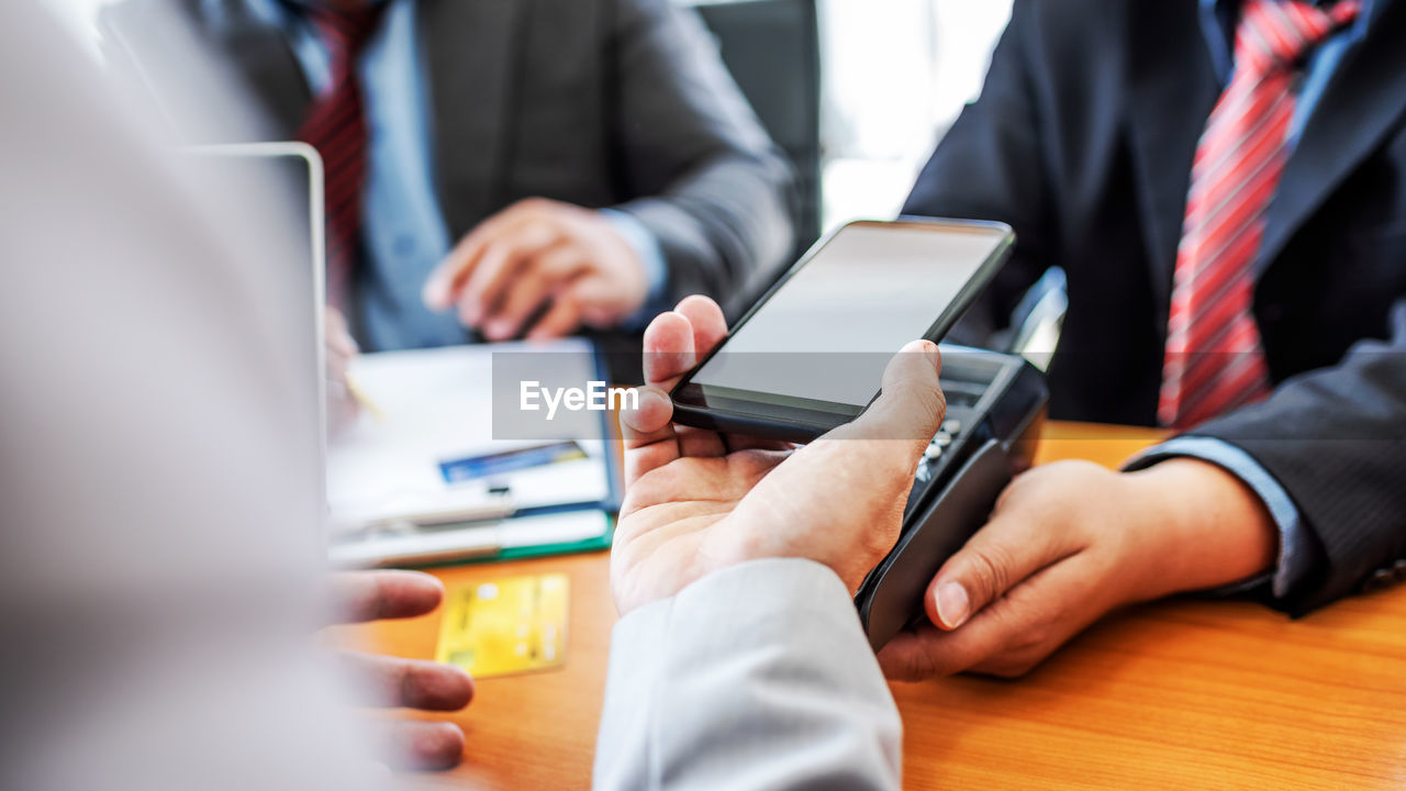 wireless technology, technology, communication, connection, business, table, business person, office, men, hand, businessman, selective focus, adult, indoors, midsection, portable information device, human hand, human body part, smart phone, screen, teamwork, coworker