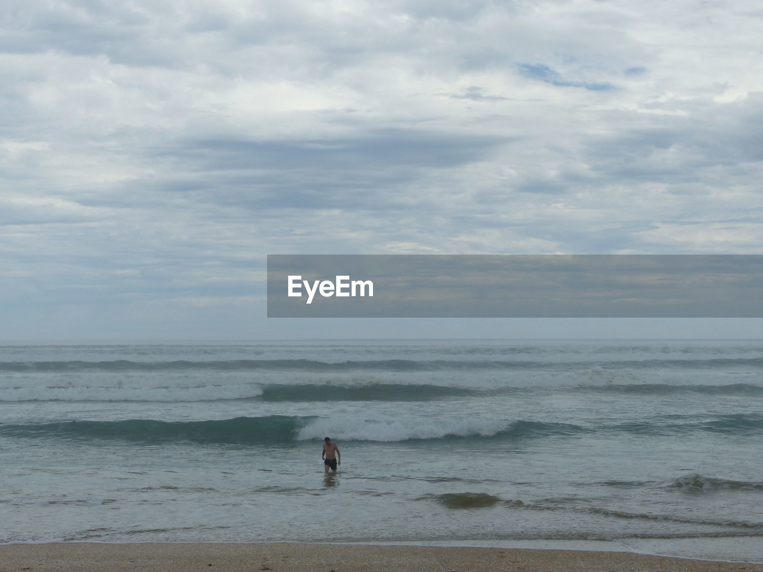 Mid distance of man wading in sea against cloudy sky