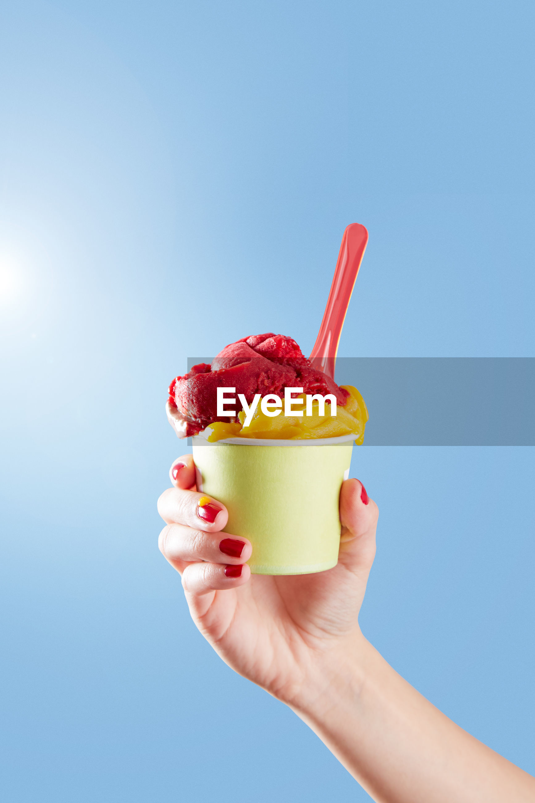 Close-up of hand holding ice cream cup against sky