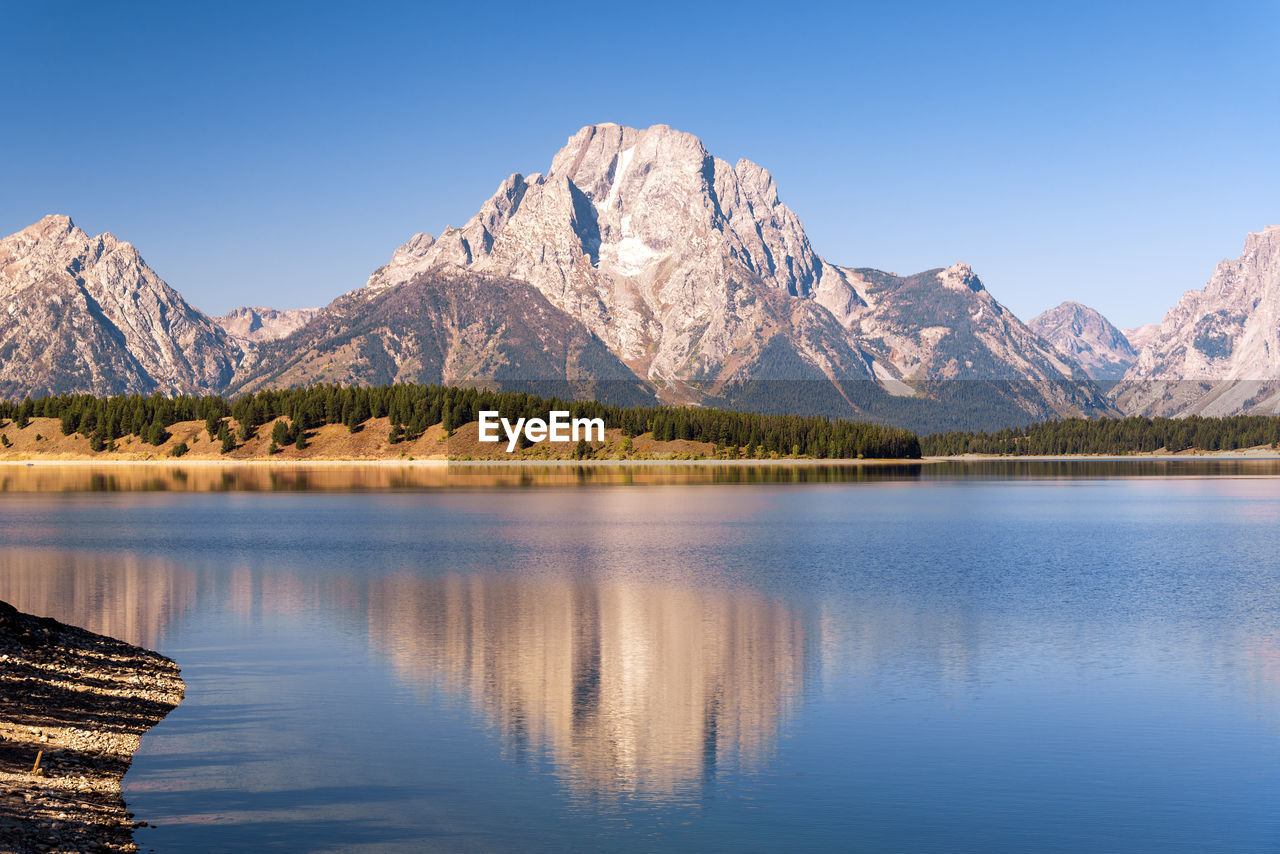 mountain, mountain range, reflection, scenics, lake, beauty in nature, nature, tranquility, blue, tranquil scene, idyllic, outdoors, no people, waterfront, water, day, clear sky, rocky mountains, landscape, snow, sky, tree