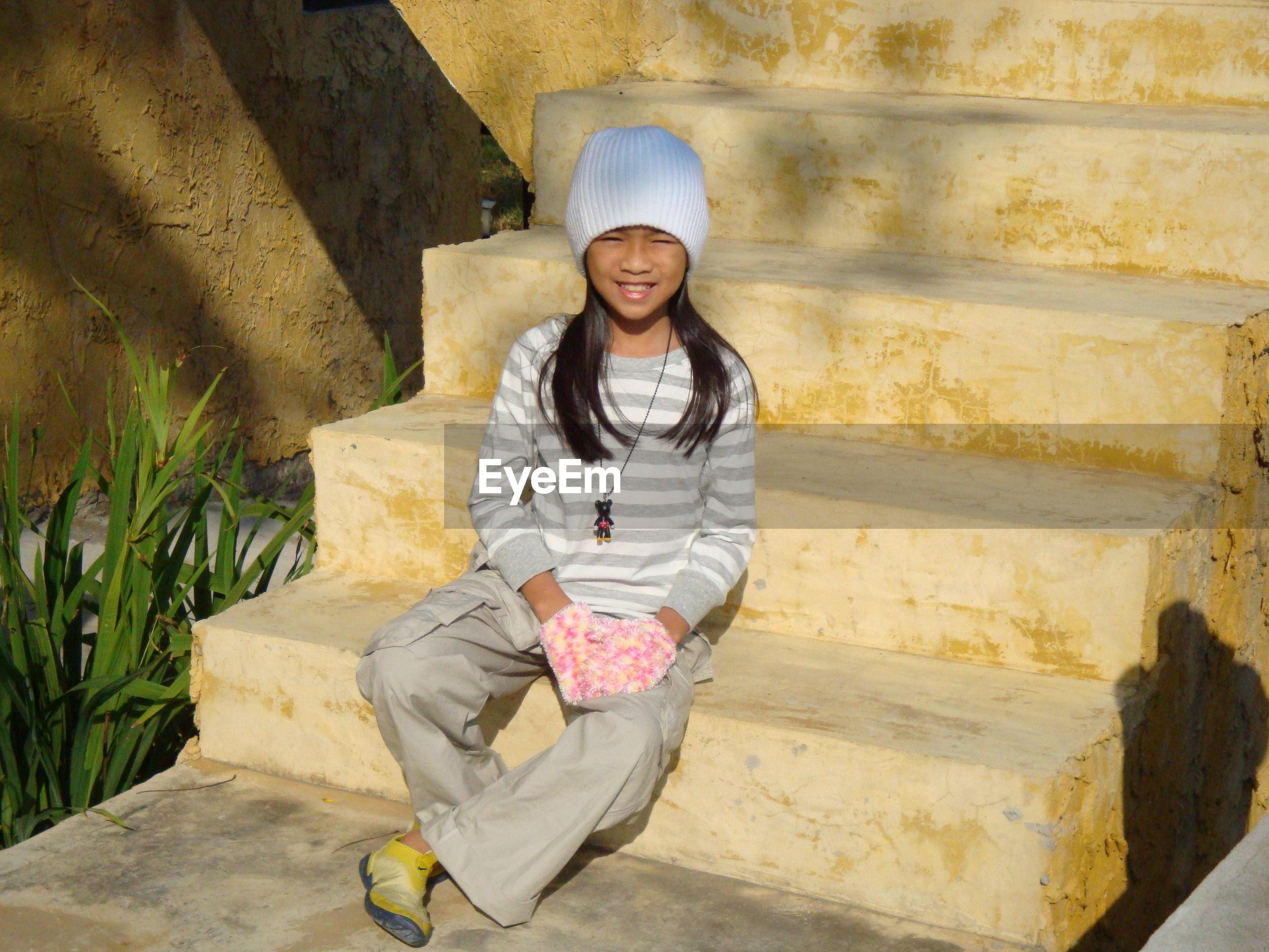 Full length portrait of girl sitting on steps