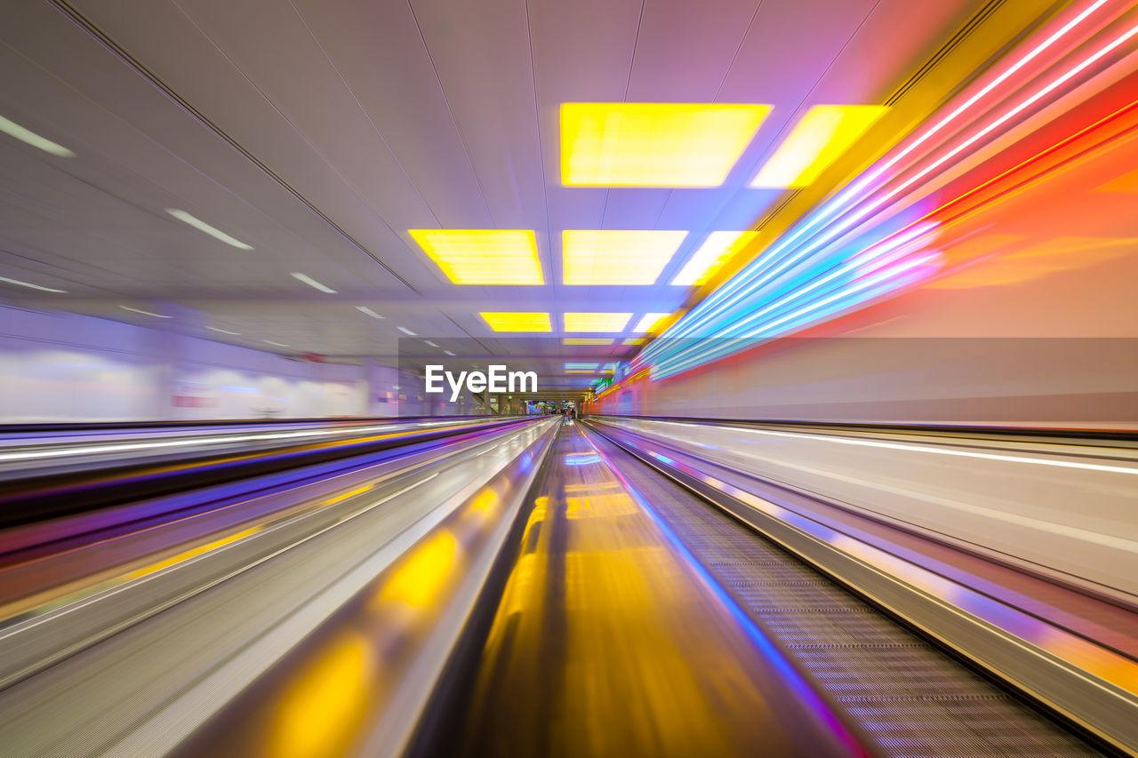 Blurred Motion Of Illuminated Moving Walkway At Airport