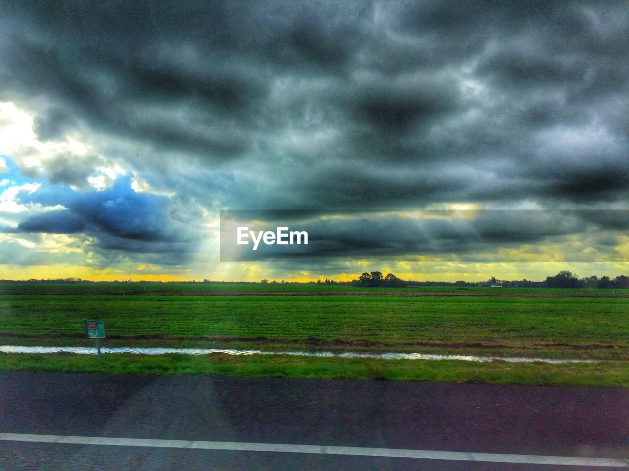 cloud - sky, landscape, field, nature, beauty in nature, scenics, weather, tranquility, tranquil scene, sky, rural scene, dramatic sky, agriculture, grass, no people, idyllic, storm cloud, outdoors, day, tree, thunderstorm