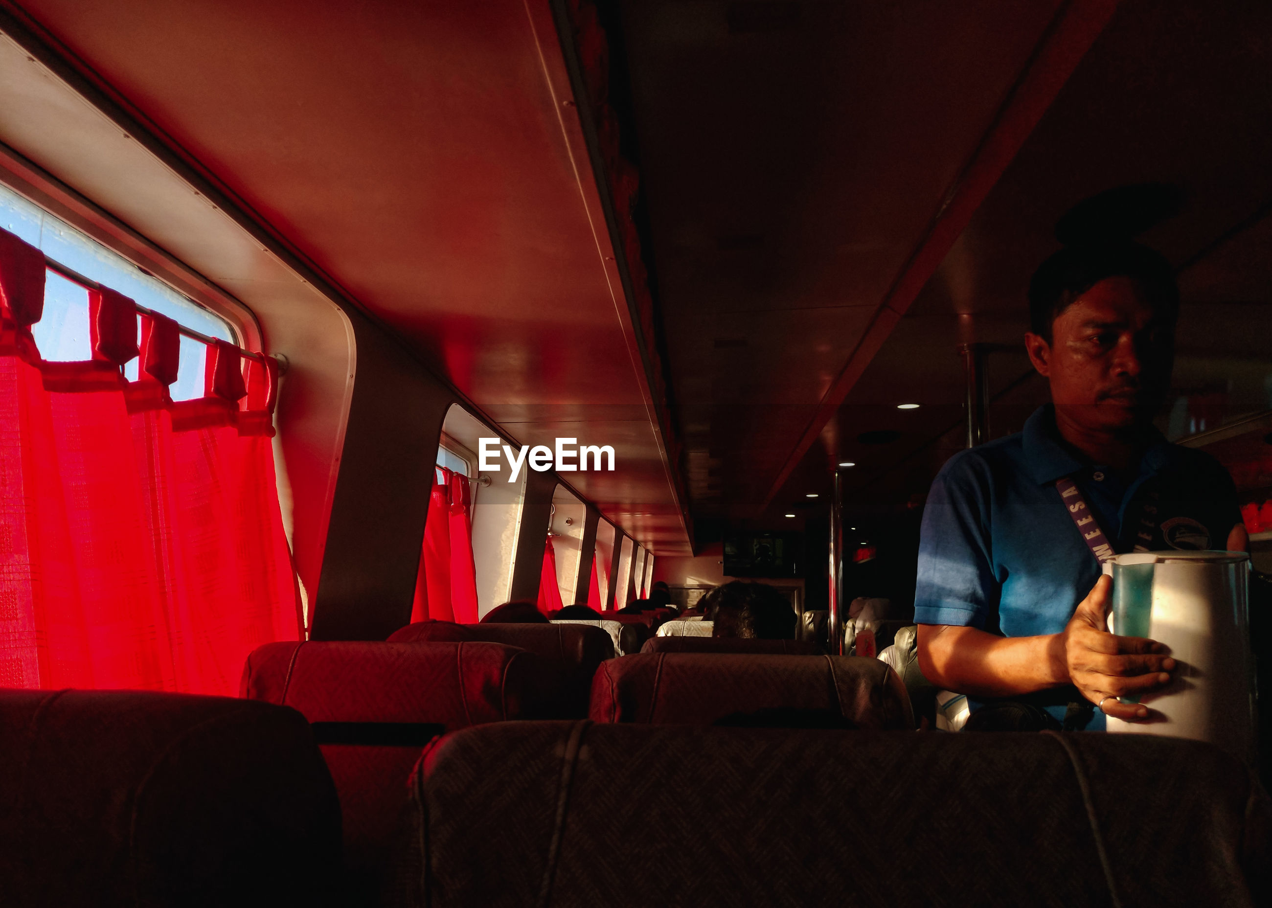 MAN SITTING ON SEAT IN BUS