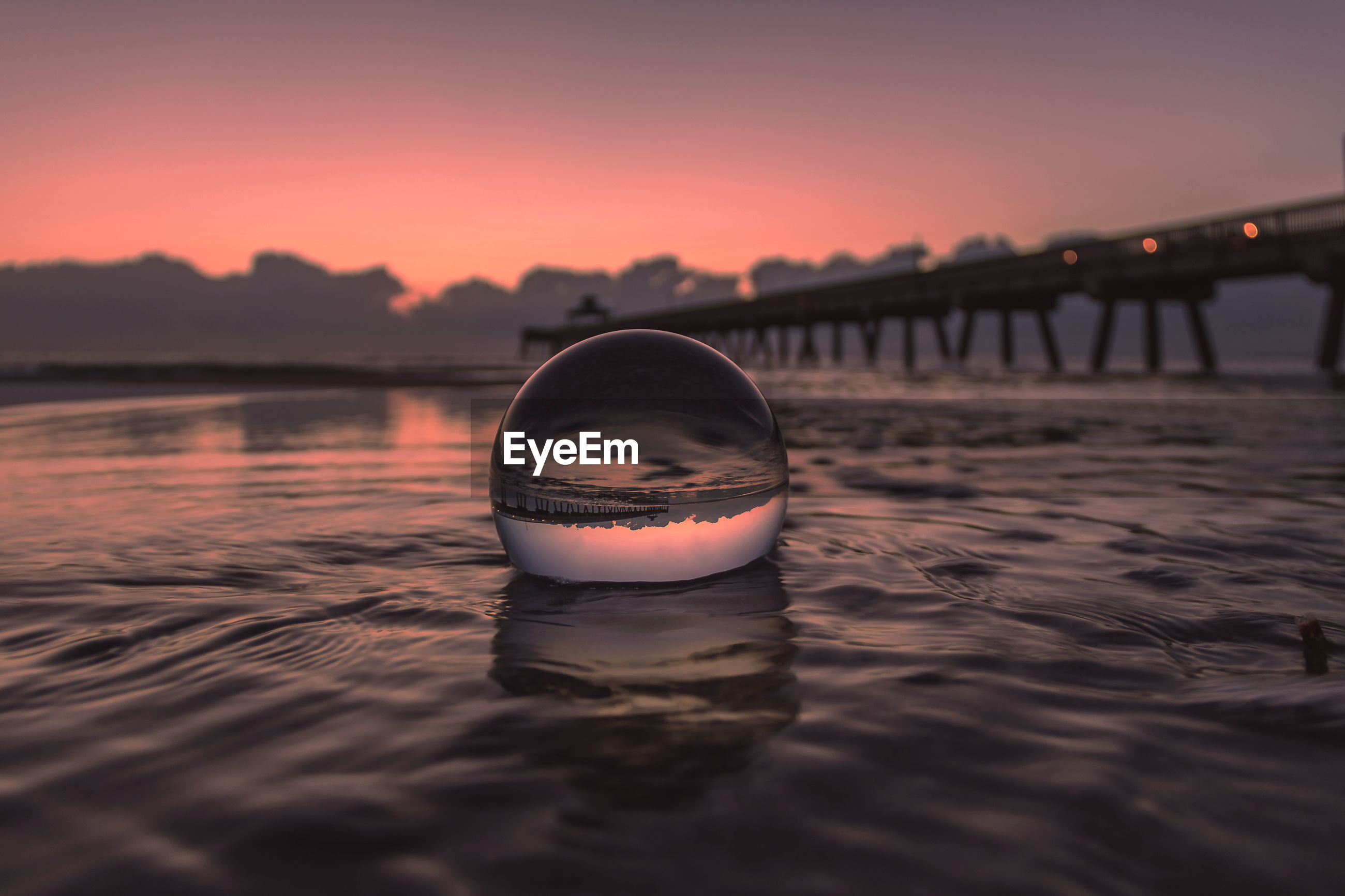 Reflection of calm sea in transparent ball