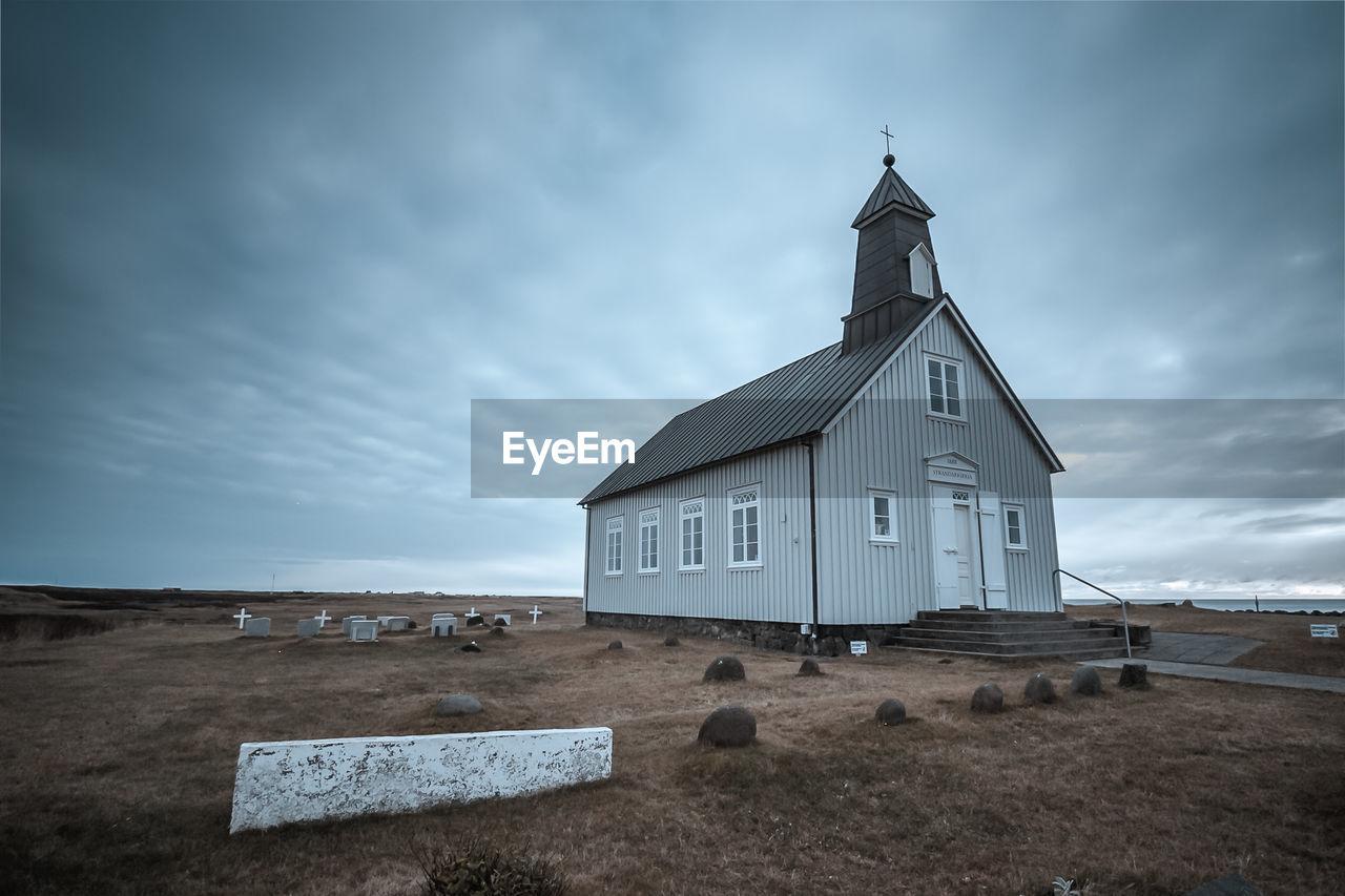 Church by cemetery against cloudy sky