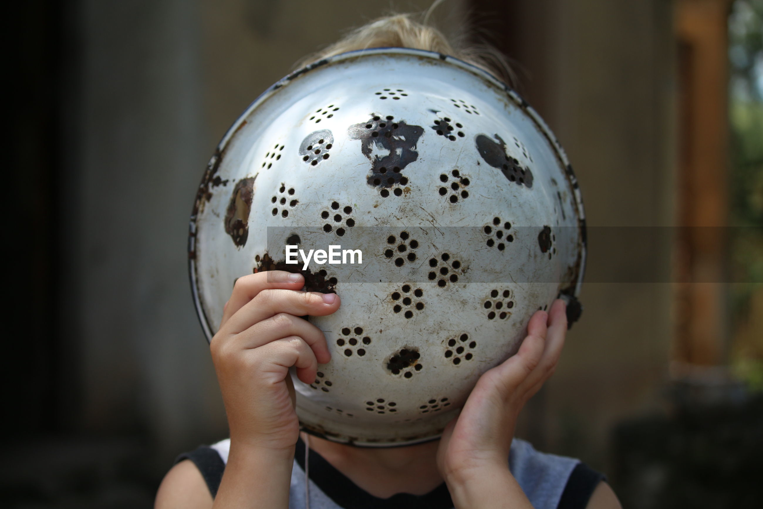 Close-up of boy covering face with colander at home