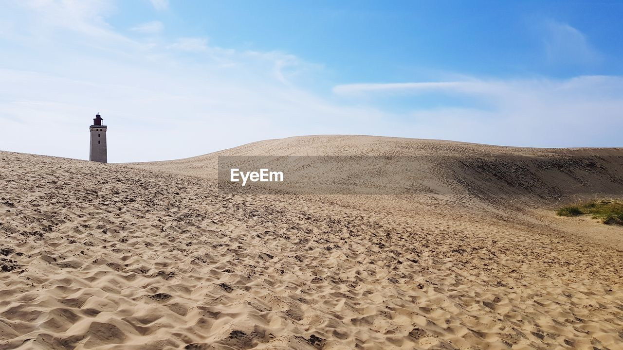 sand, land, sky, scenics - nature, sand dune, nature, architecture, beauty in nature, beach, built structure, tranquility, tranquil scene, building exterior, non-urban scene, cloud - sky, direction, lighthouse, day, landscape, desert, guidance, no people, outdoors, climate, arid climate