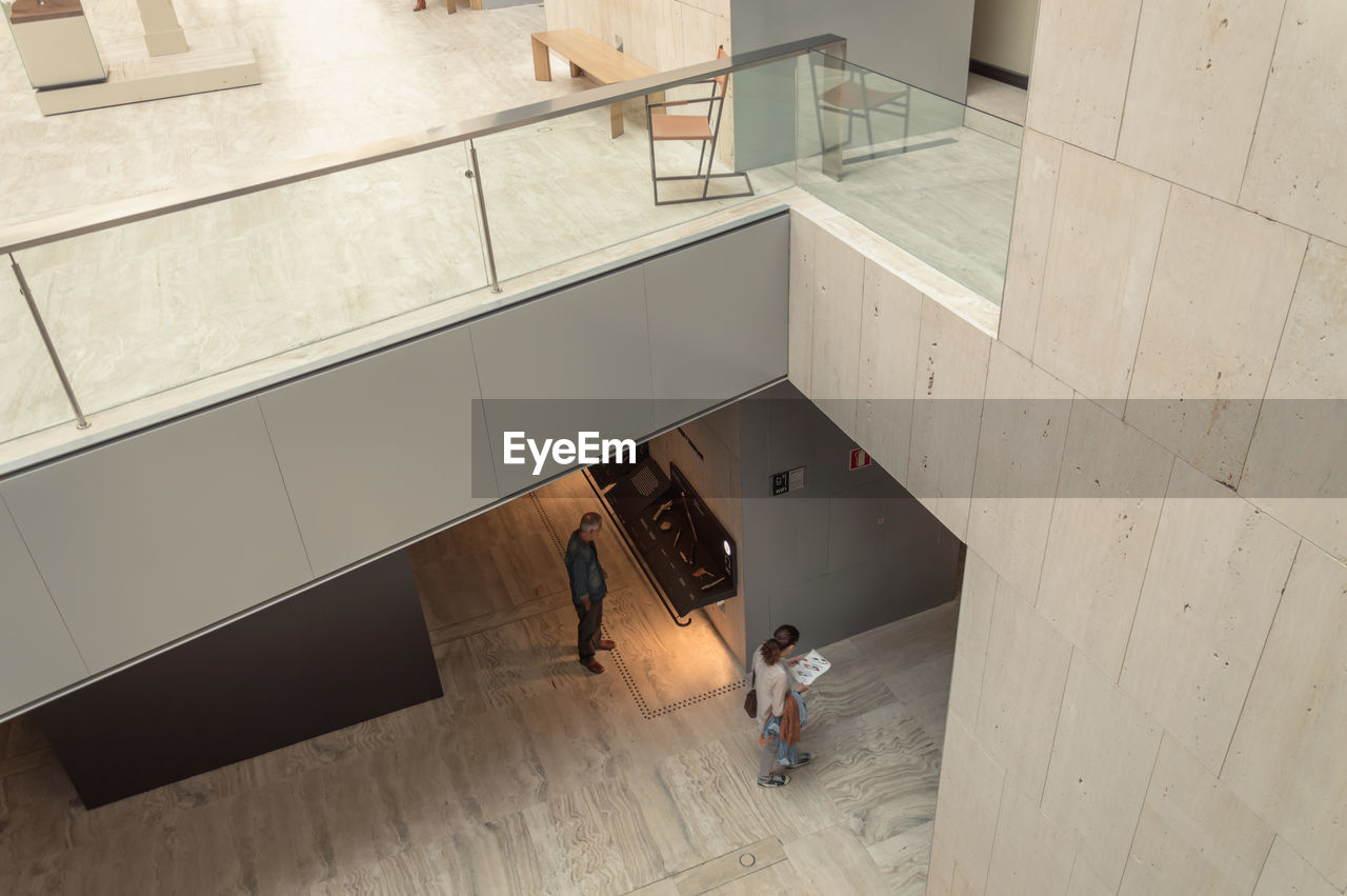 high angle view, real people, indoors, architecture, built structure, lifestyles, full length, men, standing, day, women, one person, young adult, mammal, people