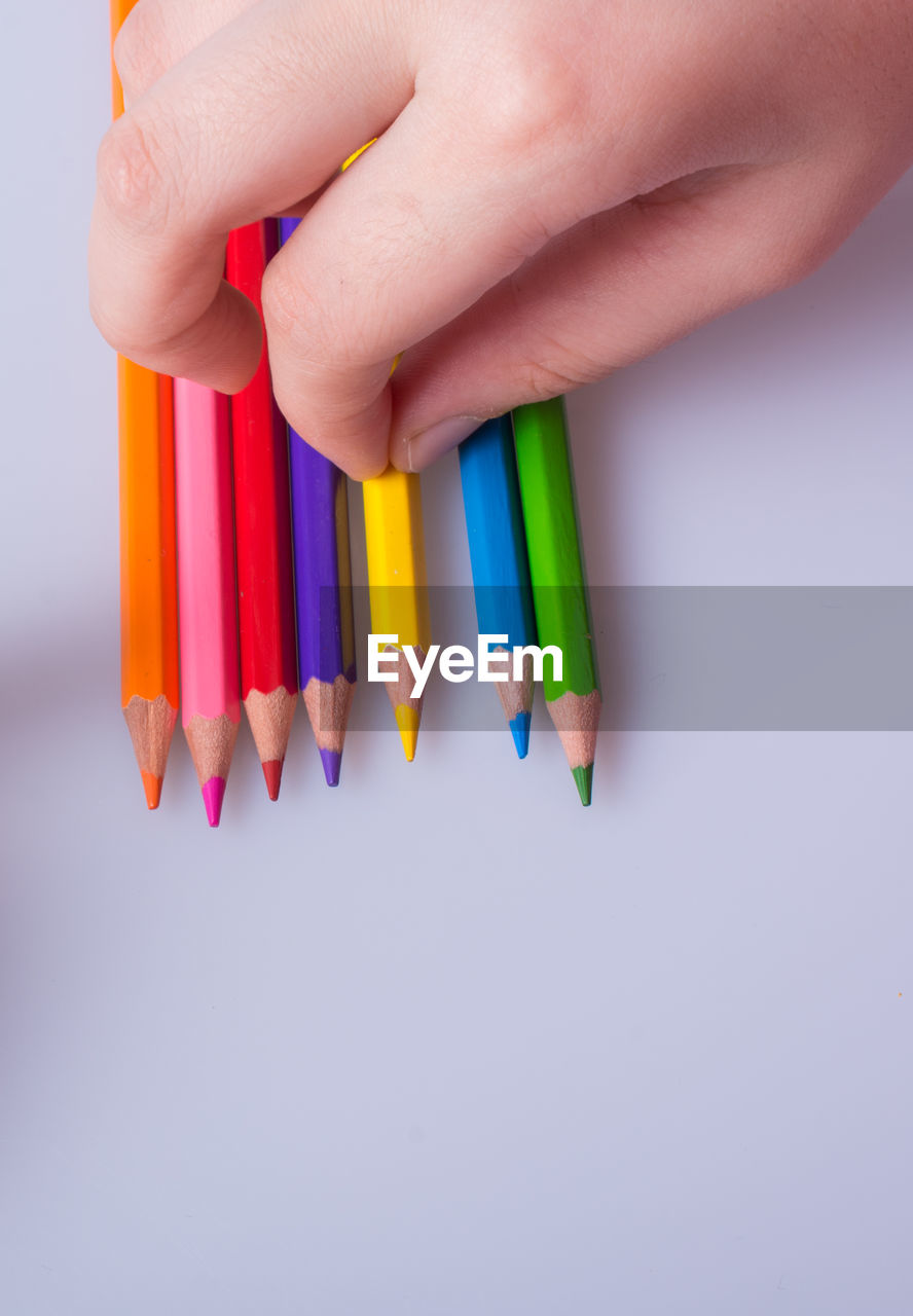 multi colored, human hand, white background, indoors, art and craft, hand, studio shot, variation, close-up, creativity, human body part, choice, one person, pencil, real people, craft, high angle view, art and craft equipment, writing instrument, body part, finger, colored pencil