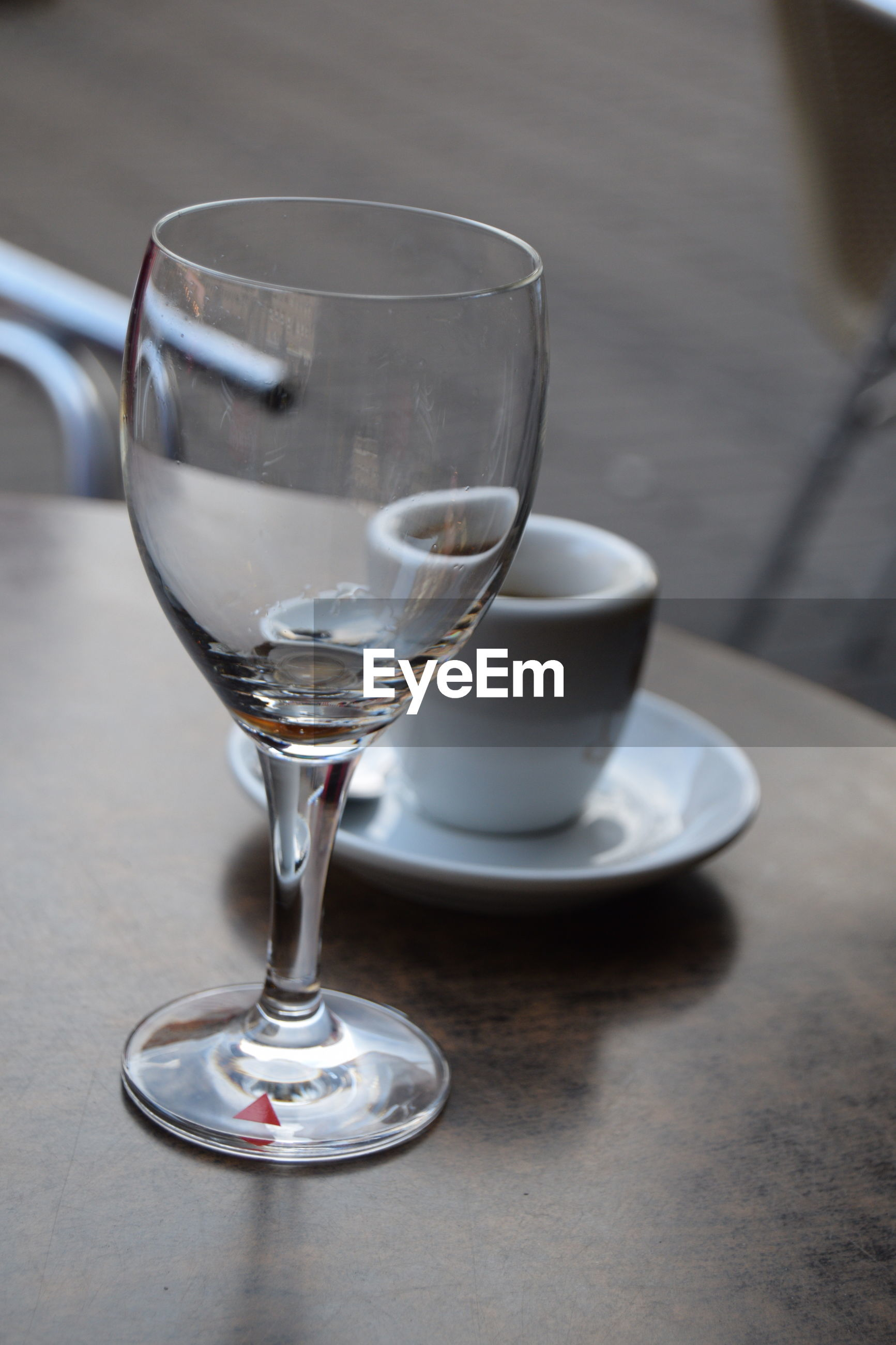 Close-up of coffee cup and wineglass on table