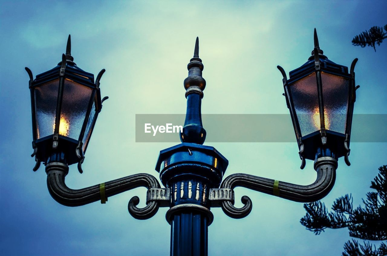 Low angle view of old gas light against sky at dusk