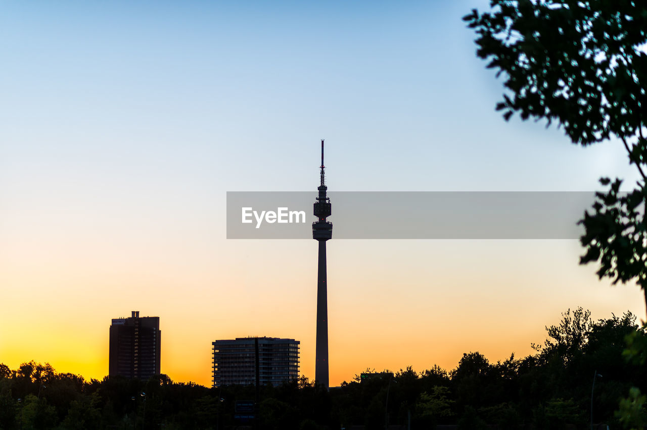 sky, architecture, built structure, building exterior, sunset, tree, tower, tall - high, plant, communication, nature, silhouette, city, building, no people, clear sky, travel, tourism, travel destinations, outdoors, global communications, office building exterior, spire, skyscraper