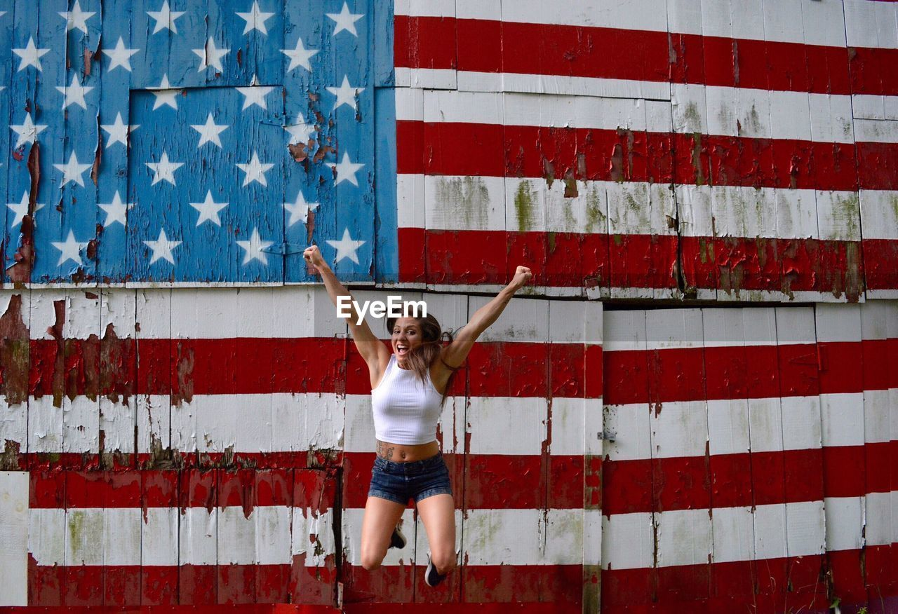 Excited Woman Jumping Against American Flag Painted On Wall