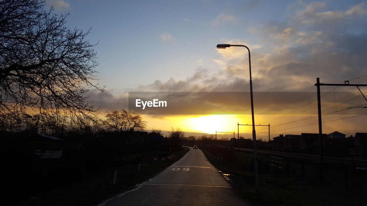 sunset, transportation, road, sky, street light, the way forward, car, cloud - sky, no people, nature, outdoors, scenics, silhouette, land vehicle, tree, beauty in nature, bare tree, day
