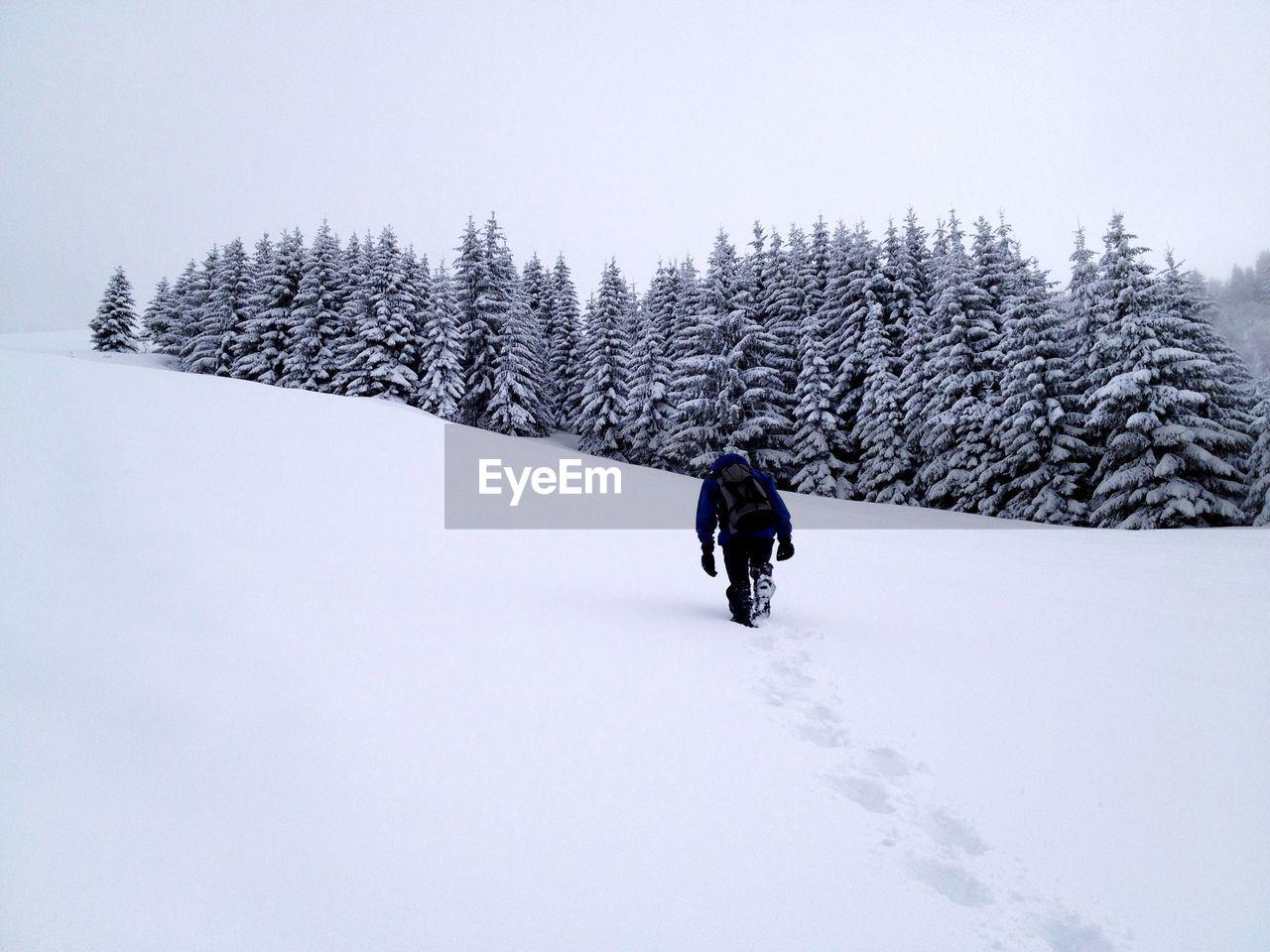 Man Hiking On Snowy Field Against Sky
